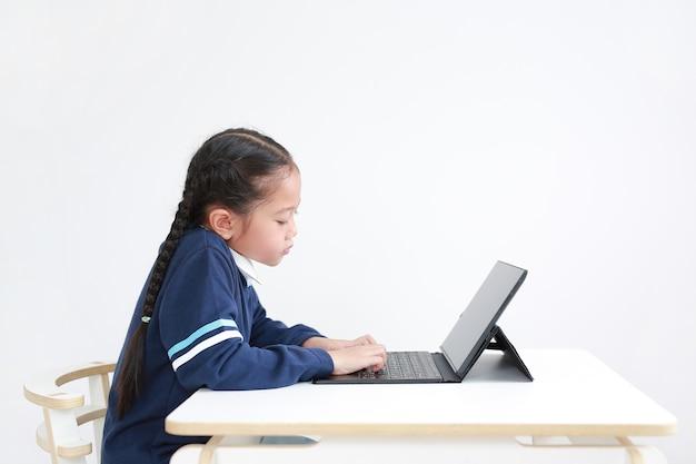 Portret aziatisch klein kindmeisje in schooluniform die laptop op geïsoleerde lijst met behulp van