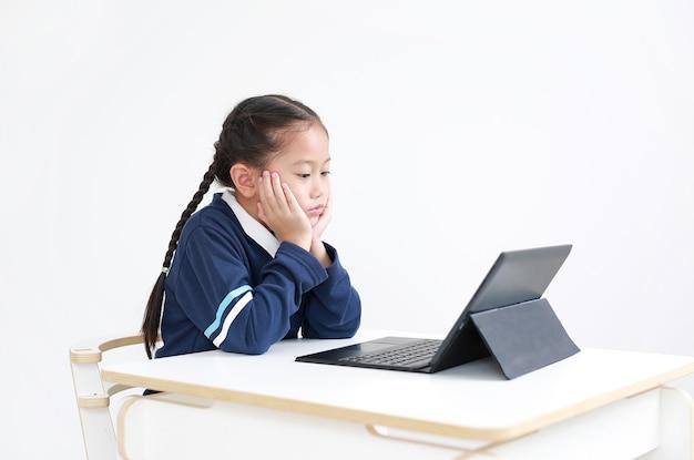 Portret aziatisch klein kindmeisje in schooluniform met behulp van laptop op tafel geïsoleerd op wit