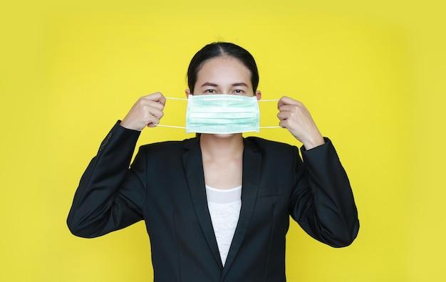 Portret aziatische bedrijfsvrouw die medisch die beschermingsmasker draagt op gele achtergrond wordt geïsoleerd.
