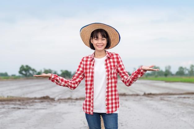 Portret aziatische boer vrouw staande en handen opsteken met een glimlach op de rijstboerderij