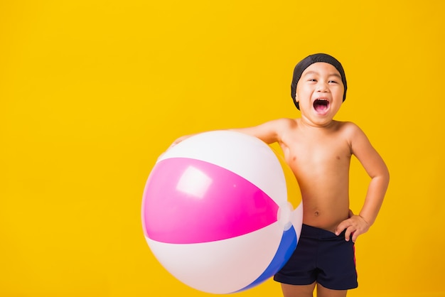 Portret aziatische gelukkig weinig kindjongen die in het strandbal glimlachen van de zwempakgreep