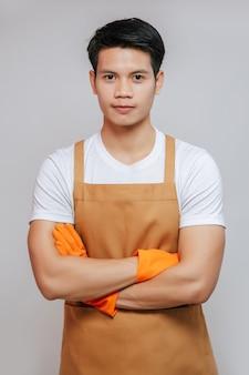 Portret aziatische jonge knappe man staat met gekruiste armen, hij draagt een schort en rubberen handschoenen, glimlacht en kijkt naar de camera, kopieert ruimte