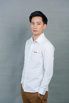 Portret aziatische jonge man op grijs, tiener