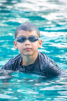 Portret aziatische jongen die zwembril in de pool draagt.