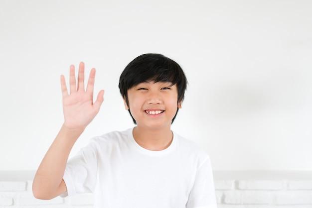 Portret aziatische jongen zwaaiende hand voor groet Premium Foto