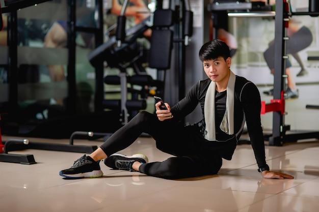 Portret aziatische knappe man met sportkleding en smartwatch zittend op de vloer en mobiele telefoon gebruiken na het sporten in de sportschool, glimlachen en