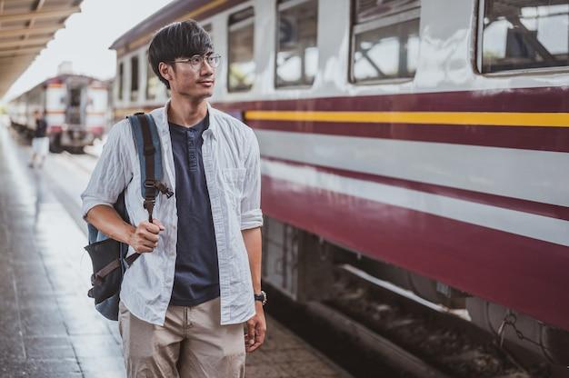 Portret aziatische man lopen op een trein op een treinstation voor een vakantie. reisconcept. man reiziger toerist wandelen op treinstation.