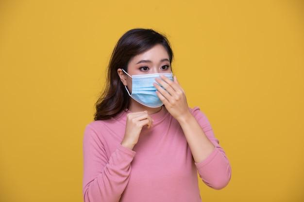 Portret aziatische mooie gelukkige jonge vrouw die gezichtsmasker of beschermend masker draagt tegen coronaviruscrisis of covid-19-uitbraak op gele achtergrond