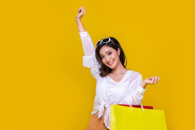Portret aziatische mooie gelukkige jonge vrouw die vrolijk glimlacht en boodschappentassen houdt die op gele studioachtergrond worden geïsoleerd.