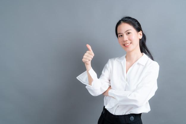 Portret aziatische mooie jonge vrouw permanent, ze maakte vinger duimen omhoog op grijs oppervlak