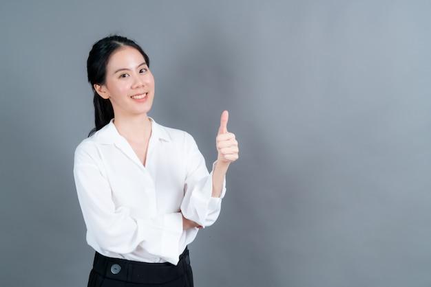 Portret aziatische mooie jonge vrouw permanent, ze maakte vinger duimen omhoog op grijze achtergrond