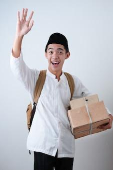 Portret aziatische moslim man tegen op grijs moslim kleding dragen en doos te houden