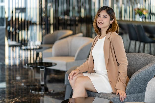 Portret aziatische onderneemster die formele kostuumzitting op de bank in moderne hal draagt