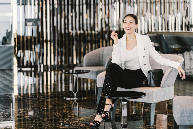 Portret aziatische onderneemster die formele kostuumzitting op de bank in moderne hal, kantoor of coworking ruimte, koffiepauzevrije tijd, mode en levensstijl na werktijd, bedrijfsmensenconcept dragen