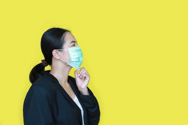 Portret aziatische onderneemster die medisch beschermingsmasker draagt dat op geel wordt geïsoleerd