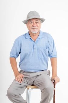 Portret aziatische senior man, oude man, voel me gelukkig goede gezondheid met een hoed en een wandelstok geïsoleerd op een witte achtergrond - levensstijl senior mannelijke concept