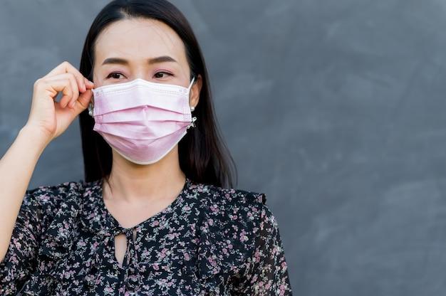 Portret aziatische vrouw dragen gezichtsmasker met kale cement oppervlak
