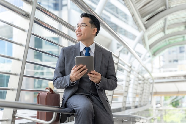 Portret aziatische zaken man zaken district, senior visionaire leidinggevenden leider met zakelijke visionled telefoon computer in de hand - levensstijl mensen bedrijfsconcept