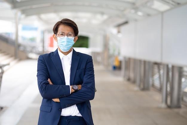 Portret aziatische zakenman die een beschermend gezichtsmasker draagt, voorkomt dat het covid-19-virus buiten in de stad staat. lege banner voor tekstachtergrond.