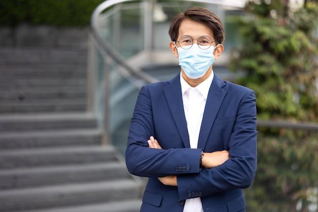 Portret aziatische zakenman die een beschermend gezichtsmasker draagt, voorkomt dat het covid-19-virus buiten in de stad staat.