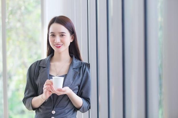 Portret aziatische zakenvrouw met lang haar staat en houdt 's ochtends een koffiekopje in haar handen