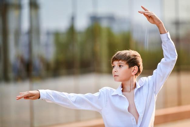 Portret ballet jongen oefening tegen de achtergrond van stadsreflectie in glazen wand