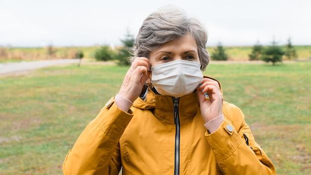 Portret bejaarde vrouw haar medische gezichtsmasker opstijgen. hogere vrouw die een beschermend masker buiten bij koud weer draagt.