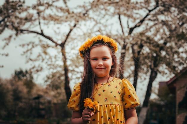 Portret bij zonsondergang van een schattig charmant meisje in een jurk en een krans van paardebloemen op haar hoofd een meisje ...