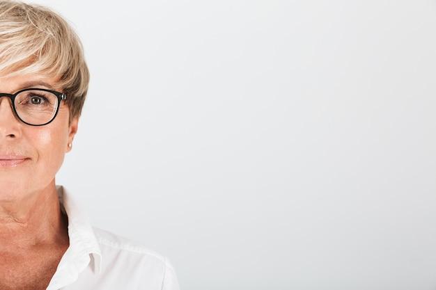 Portret bijgesneden van een tevreden vrouw van middelbare leeftijd met een bril die naar een camera kijkt die over een witte muur in de studio is geïsoleerd;