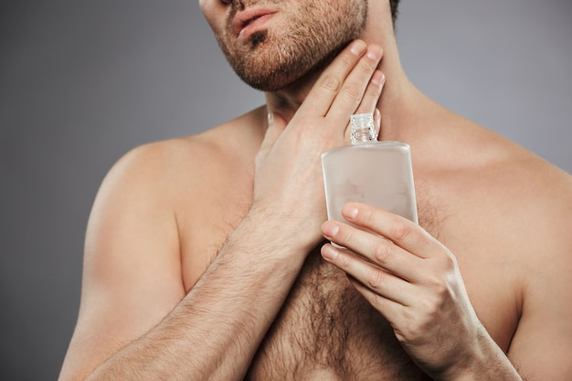 Portret bijgesneden van knappe halfnaakte man zetten parfum op zijn nek, geïsoleerd over grijze muur