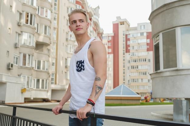 Portret blonde hipster jongen met tatoeages en stijlvol haar