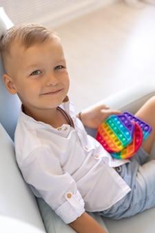 Portret blonde jongen met pop it zintuiglijk speelgoed verschillende vormen