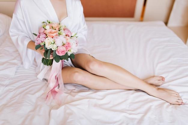 Portret bruid in witte badjas en boeket bloemen op bed in de ochtend