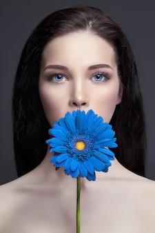 Portret brunette vrouw met blauwe bloem in de hand