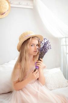 Portret charmante jonge blonde meisje in strooien hoed. meisje met een boeket van slavender in huis.