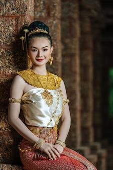 Portret charmante thaise vrouw in mooi traditioneel klederdrachtkostuum, vrouw die typische thaise kleding draagt die in archeologische plaats of thaise tempel zit, identiteitscultuur van thailand