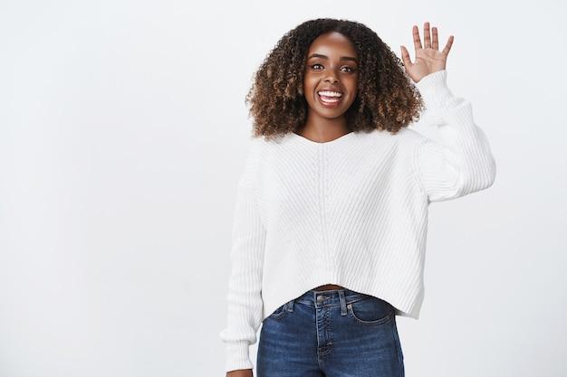 Portret charmante vriendelijke lachende aangename afro-amerikaanse vrouw hand opsteken zwaaiende groet buurman zeg hallo, gastvrije vrouw ontmoet haar luchthaven, witte muur