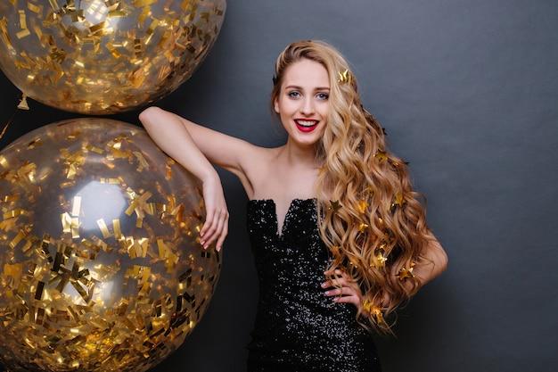 Portret charmante vrolijke jonge vrouw in zwarte luxe jurk, met lang blond krullend haar, grote ballonnen vol met gouden tinsels. verjaardagsfeestje vieren, positiviteit uitdrukken.