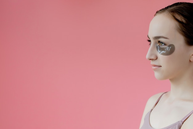 Portret close-up lachende jonge vrouw met onder de ogen hydraterende patches masker, huidverzorging procedure.
