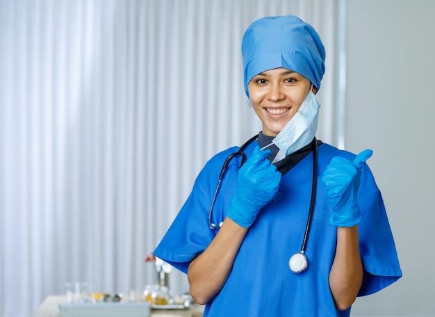 Portret close-up shot van gelukkige mooie vrouwelijke vrijheidsdokter draagt blauw ziekenhuispak met stethoscoop glimlachend duim omhoog wanneer opstijgen gebruikt chirurgisch gezichtsmasker naar camera kijken terwijl pandemie eindigt.