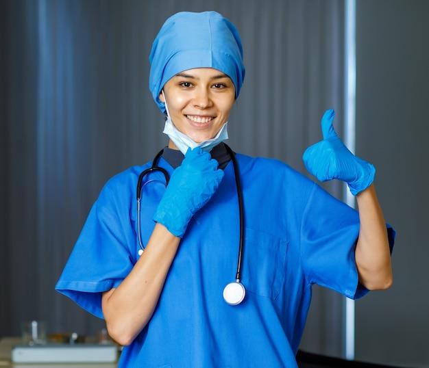 Portret close-up shot van gelukkige mooie vrouwelijke vrijheidsdokter in blauw ziekenhuispak met stethoscoop glimlachend duim omhoog wanneer opstijgen gebruikt chirurgisch gezichtsmasker naar camera kijken terwijl pandemie eindigt.