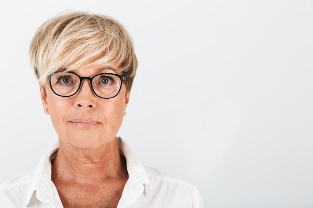 Portret close-up van een blanke vrouw van middelbare leeftijd die een bril draagt en naar een camera kijkt die over een witte muur in de studio is geïsoleerd