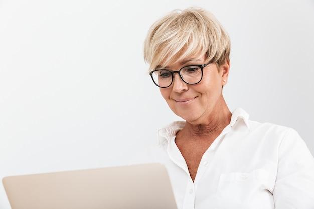Portret close-up van een blonde volwassen vrouw met een bril die lacht terwijl ze een laptopcomputer gebruikt die over een witte muur in de studio wordt geïsoleerd