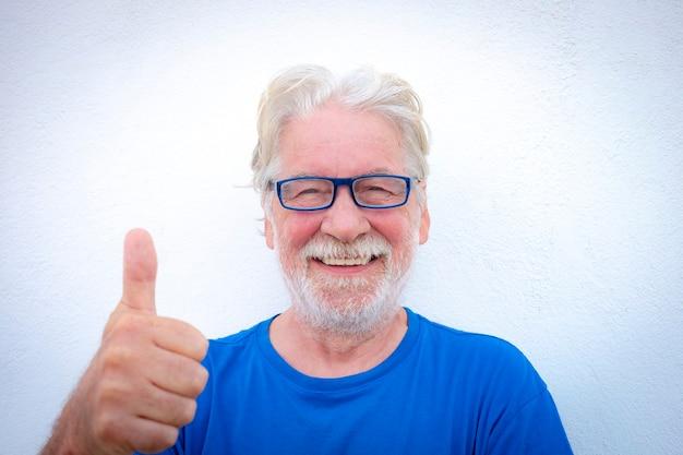 Portret close-up van een lachende senior man met witte baard op witte achtergrond met bril en tshirt in blauwe kleur. positieve gepensioneerde persoon met duim omhoog