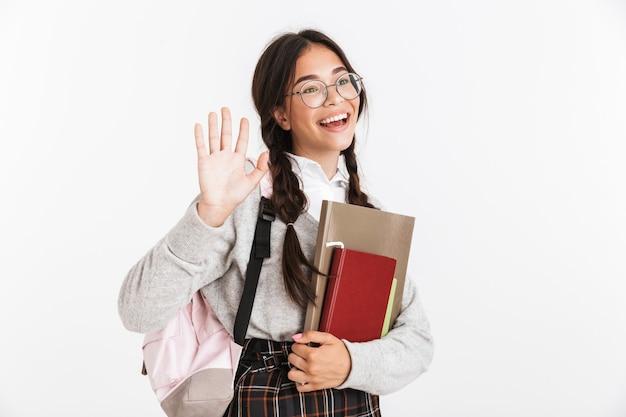 Portret close-up van een mooi tienermeisje met een bril die glimlacht en opzij zwaait terwijl ze studerende boeken vasthoudt die over een witte muur zijn geïsoleerd