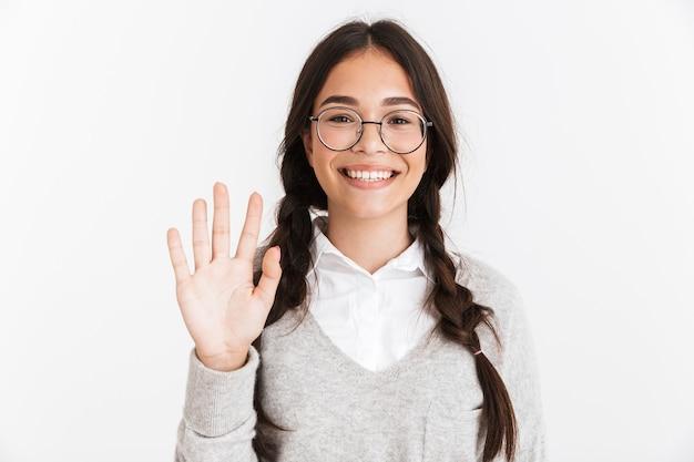 Portret close-up van een vrolijk tienermeisje met een bril en een schooluniform glimlachend terwijl ze met de hand naar de camera zwaait, geïsoleerd over een witte muur