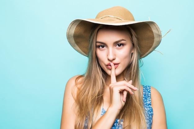 Portret close-up van europese charmante vrouw met grote strooien hoed met vinger op de lippen om geheim te houden geïsoleerd op blauwe achtergrond