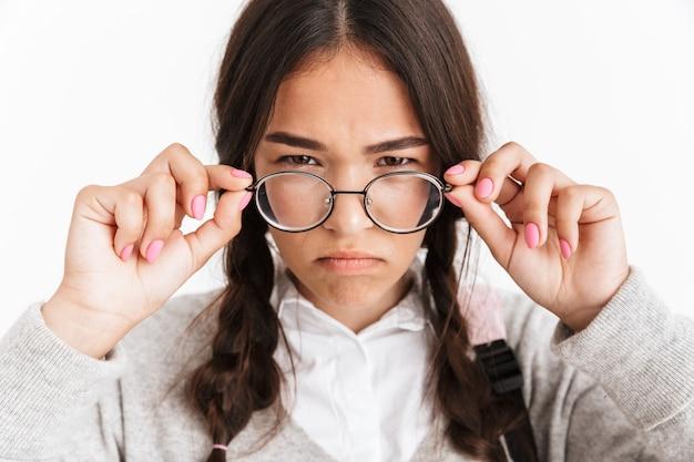 Portret close-up van gefrustreerd boos meisje met een bril die fronst en afkeer uitdrukt met gezicht geïsoleerd over witte muur