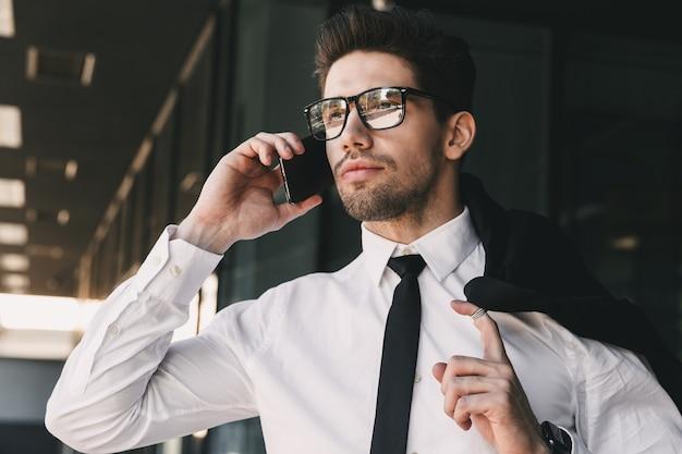 Portret close-up van jonge zakenman gekleed in formeel pak staande buiten glazen gebouw met jas over zijn schouder, en praten over de mobiele telefoon