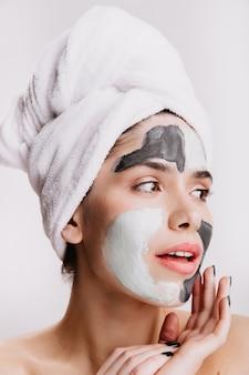 Portret close-up van mooi meisje met handdoek op nat haar. vrouw met gezichtsmasker poseren op geïsoleerde muur.